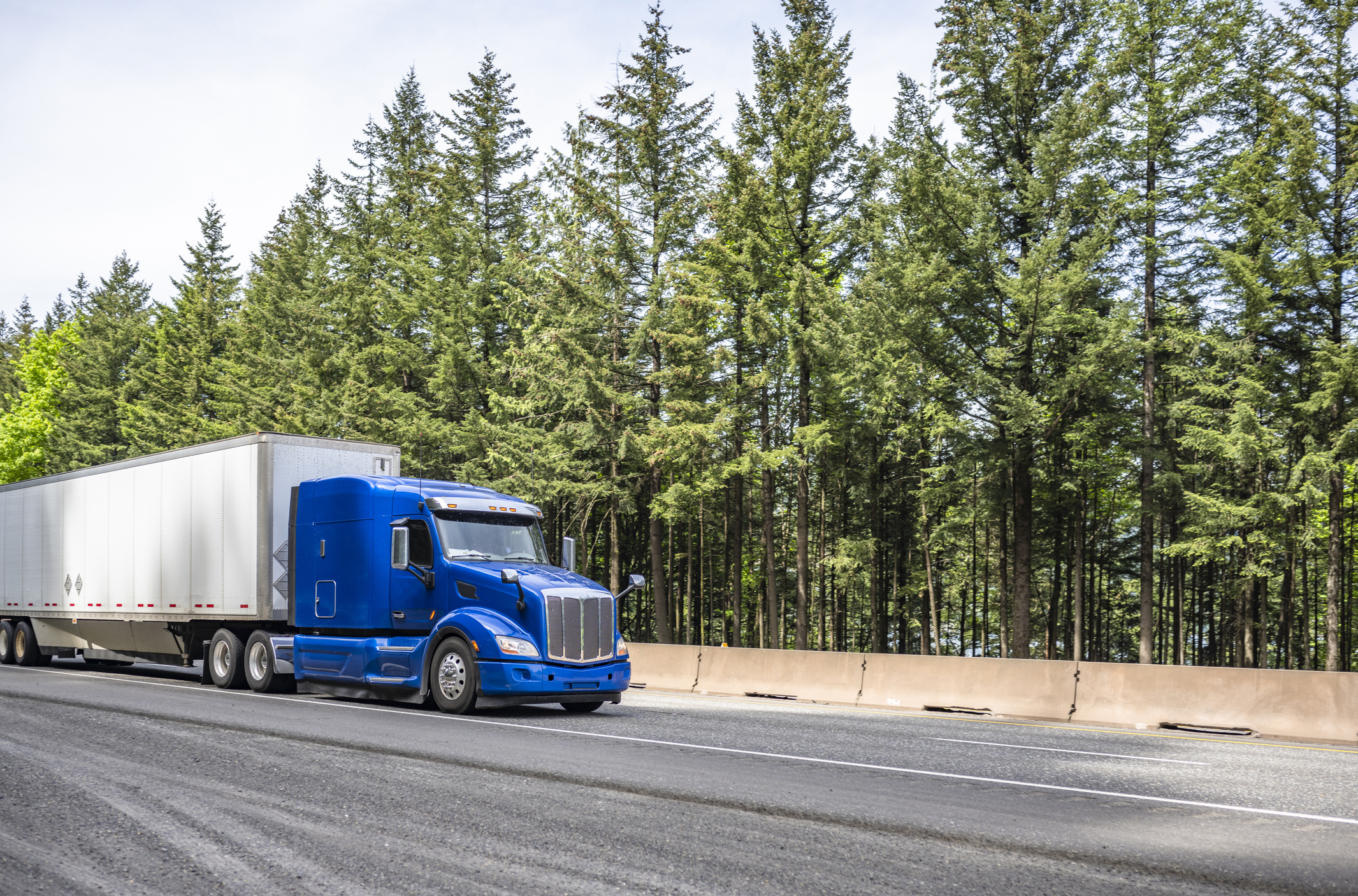 Powerful industrial long haul blue big rig semi truck transporting goods in dry van semi trailer running on the wide highway road with trees on the side